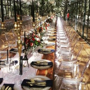 Copper and gold wedding table setting in glass marquee in forest