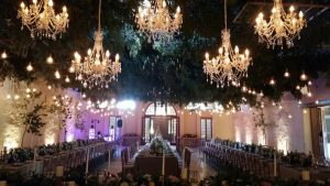 Wedding Reception with greenery and chandeliers hanging from the roof