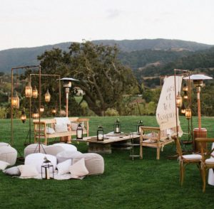 modern outdoor wedding setup with chairs, ottomans, lighting and heaters