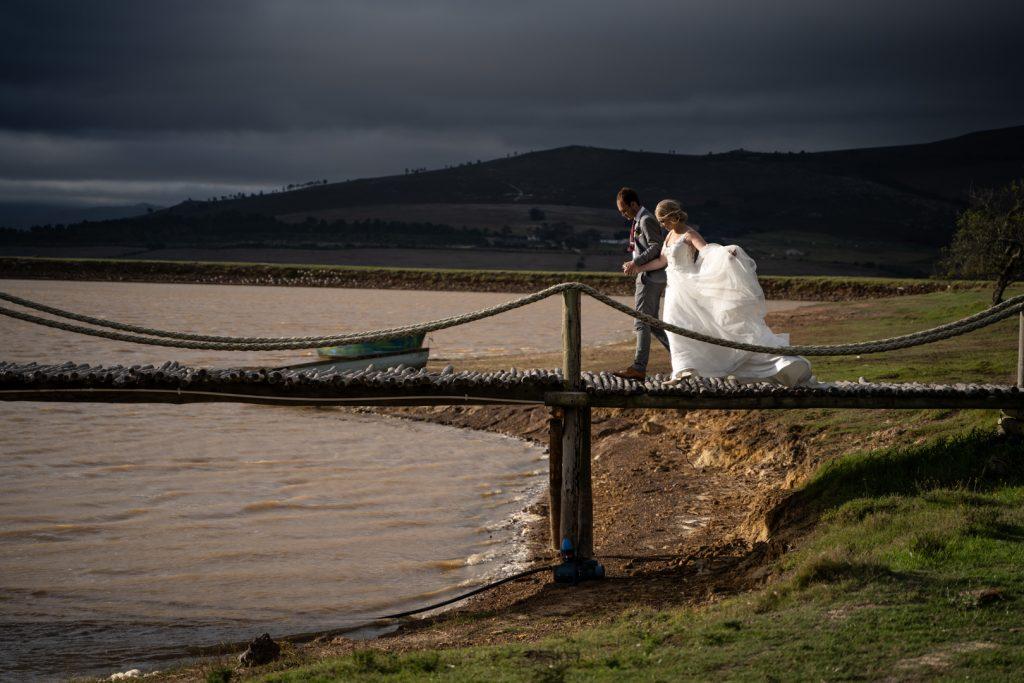 Bride and groom walking over water bridge